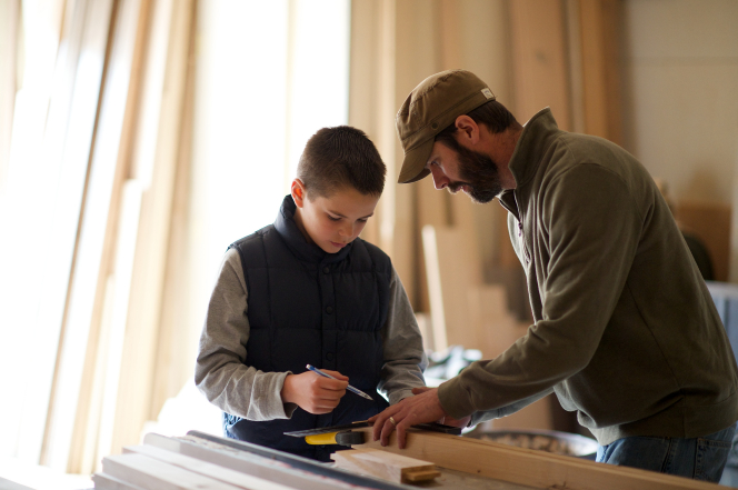 A father shows his son how to do woodworking.