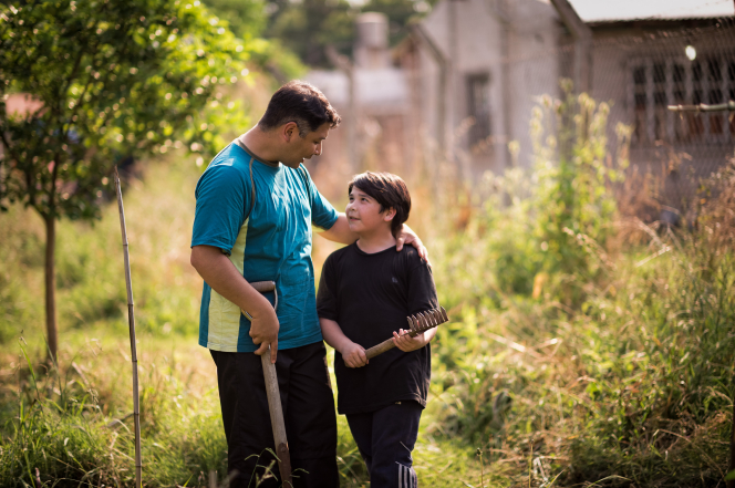 A father puts his arm around his son and talks to him while they work in a garden together.