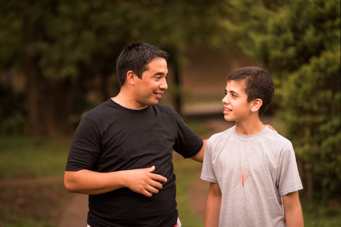A father puts his arm around his teenage son and walks and talks with him.