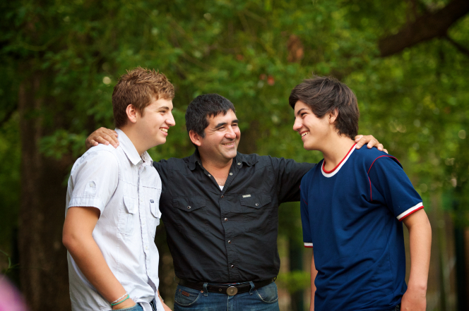 A father smiles and puts his arms around his two teenage sons.