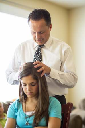 A father gives his teenage daughter a blessing by placing his hands on her head.
