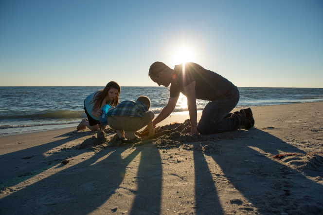 A man in a T-shirt kneels in the sand with his two children to build a sand castle together on a beach at sunset.