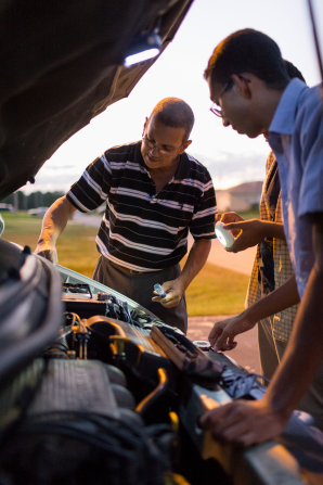 A man shows his two sons the inside of a car hood while teaching them to make some car repairs.