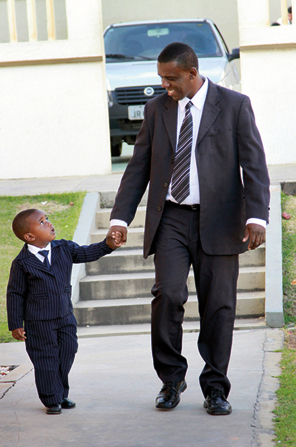 A father and son, both dressed in suits, hold hands and walk down a sidewalk.