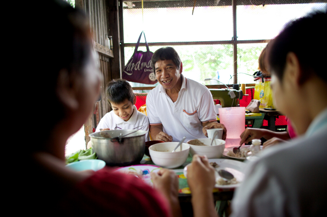 A man in a white shirt sits at a table eating dinner with his family in their home in the Philippines.