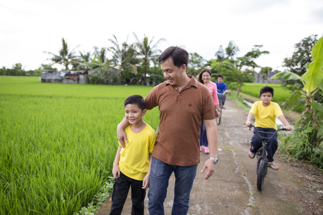 A father puts his arm around his son while the two of them walk through a lush green field ahead of the rest of the family members.