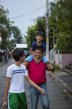 A father walks down a street while carrying one of his sons on his shoulder and talking to his other son, who walks ahead.