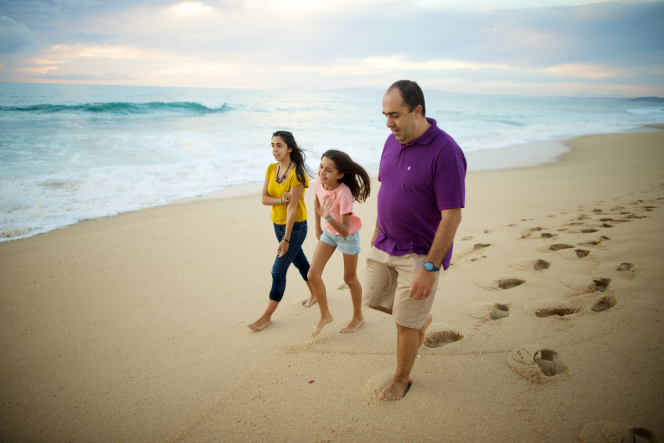 A man in a purple polo shirt walks with his two daughters on the beach, with blue waves in the background.