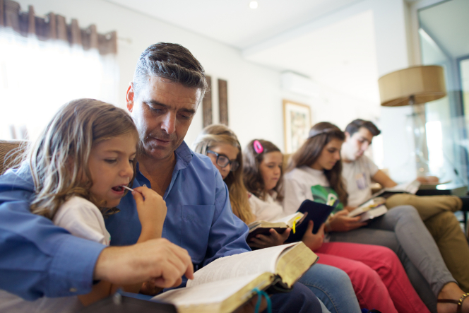 A man in a blue shirt sits with five of his children on a long couch to read the scriptures together.