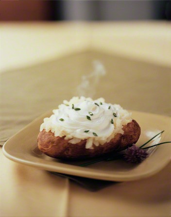 A steaming baked potato on a plate topped with sour cream and chives.