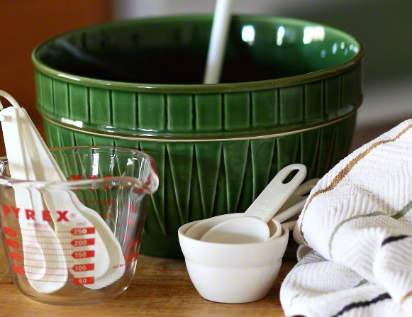 A table setting with a large green mixing bowl, measuring cups, and measuring spoons next to a dish towel.