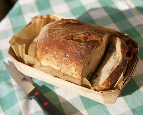 A fresh loaf of sliced bread in a basket lying next to a knife on a green and white plaid tablecloth.