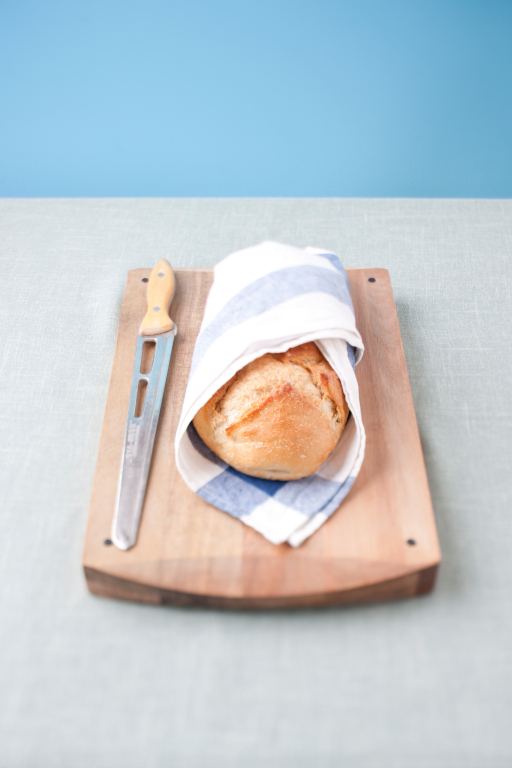 A loaf of bread wrapped in a towel on a cutting board with a knife next to it.