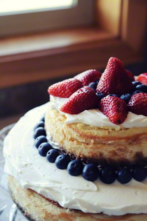 An image of a tiered cake with strawberries, blueberries, and cream.