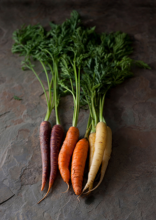 Different-colored carrots with leaves still attached.