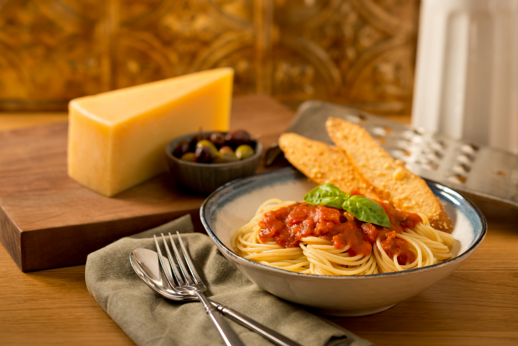 A bowl of pasta with tomato sauce and basil on top, with sliced bread, cheese, and olives next to it.