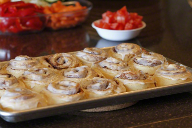 A pan of hot cinnamon rolls with icing on top, melting.