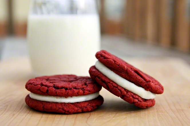 Two red velvet cookie sandwiches with a glass of milk.
