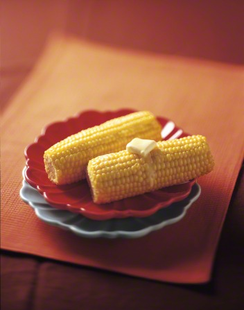 A plate with two hot cobs of corn with a chunk of butter melting on top.