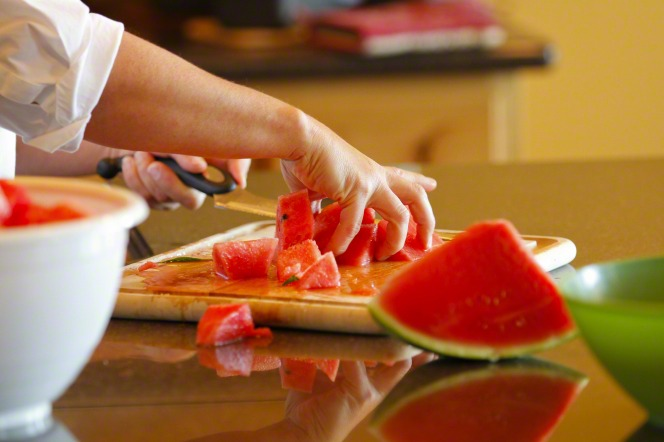 An image of hands using a knife to slice watermelon on a cutting board.