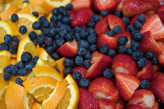 An image of sliced oranges, blueberries, and sliced strawberries.