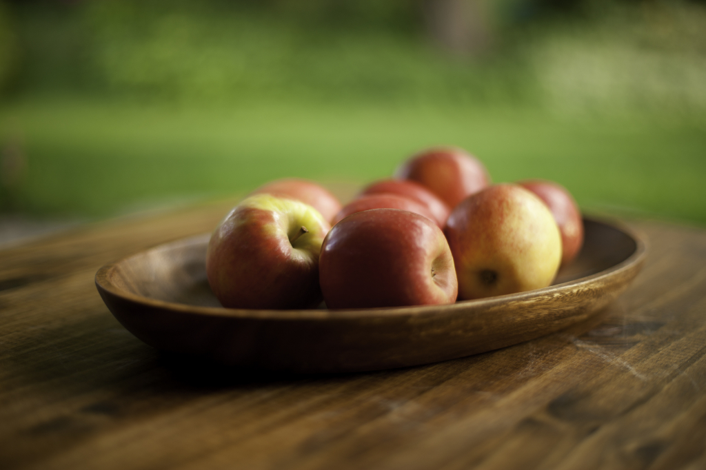 Red apples in a wooden bowl on a table outside.