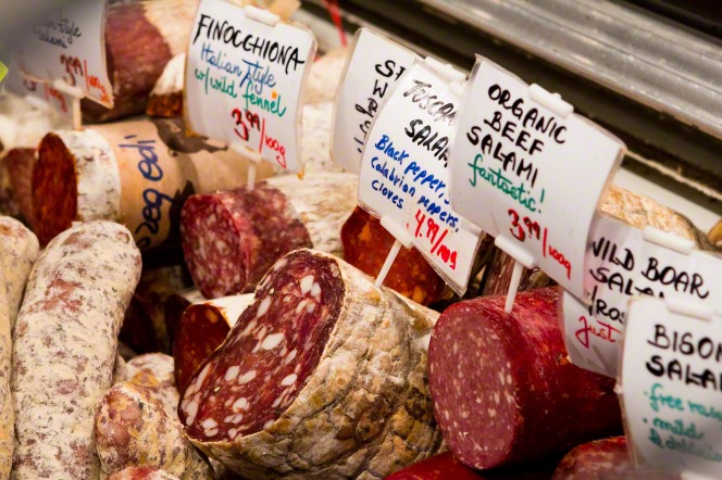 An image of different types of salami with signs displaying names and prices in a supermarket.