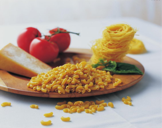 Dry macaroni and egg noodles on a wooden platter with tomatoes, basil, and cheese.