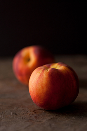 Two peaches lying on a table.