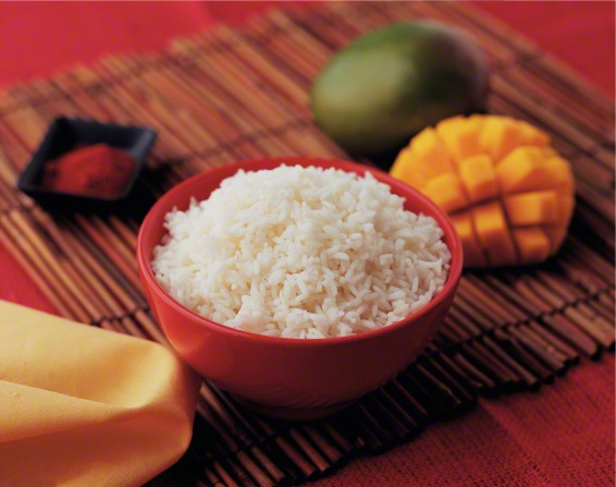 A table setting with rice in a bowl and a cut mango beside it on a red tablecloth.