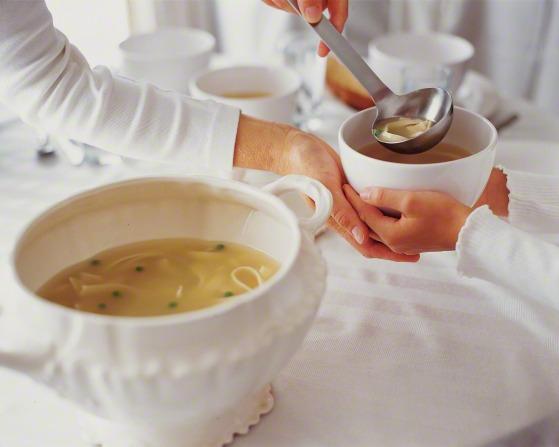 A person using a ladle to pour soup into a bowl.