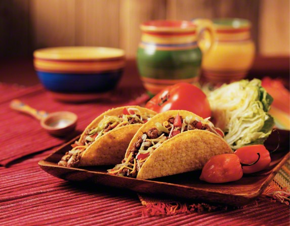 A table setting on a tray with hard-shell tacos stuffed with meat, cheese, and vegetables.