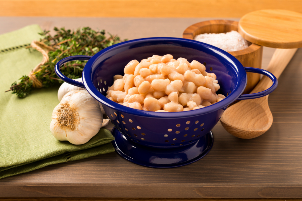 White beans in a colander, with garlic and herbs next to it.