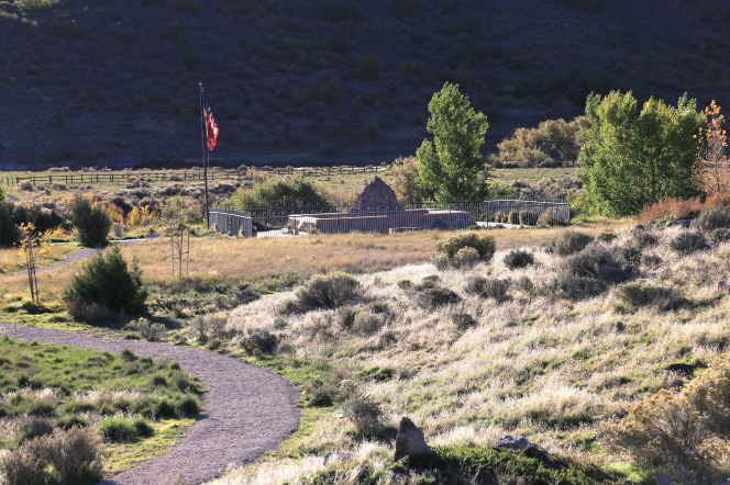 The large stone cairn at the Mountain Meadows Massacre site, with an American flag nearby.