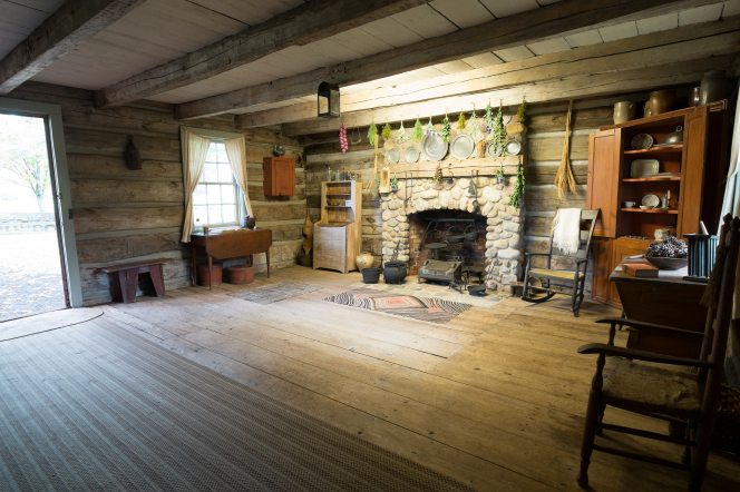 The interior of a log cabin with a stone fireplace and wooden beams holding up the ceiling.