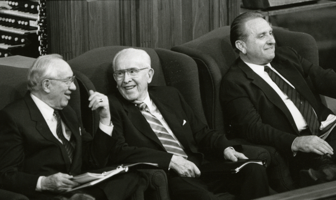 A black and white photo of Ezra Taft Benson, Gordon B. Hinckley and Thomas S. Monson smiling as they sit on the stand during General Conference.