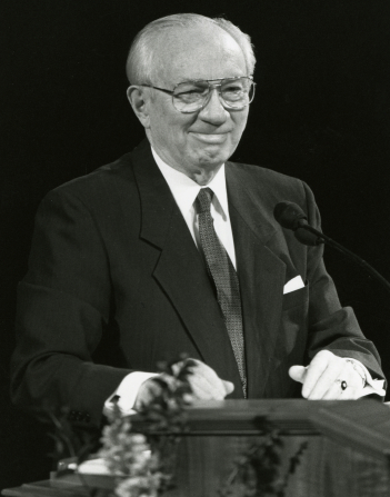 A black-and-white photo of Gordon B. Hinckley smiling from the pulpit during general conference.