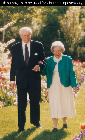 President and Sister Hinckley walking through a garden together.