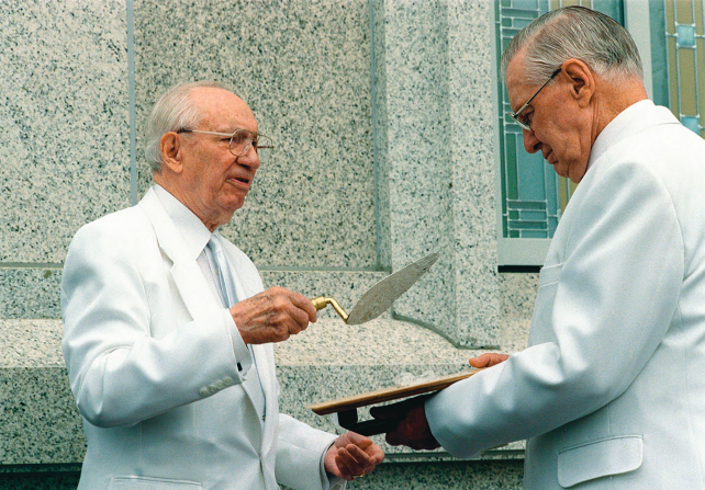 Gordon B. Hinckley and James E. Faust dressed in white, standing by a granite temple wall. President Hinckley holds a trowel, and President Faust holds out another tool toward him.