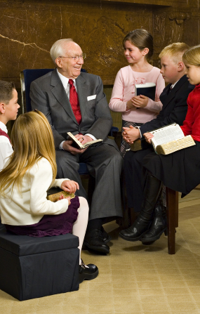 A photo of Gordon B. Hinckley sitting in a chair with children sitting around him and holding scriptures.