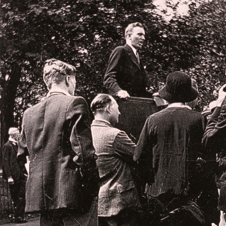 A black and white image of Gordon B. Hinckley as a young missionary speaking to a crowd.