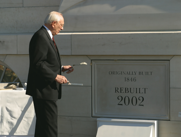 A photo of Gordon B. Hinckley holding trowels and standing next to the cornerstone at the Nauvoo Illinois Temple dedication.