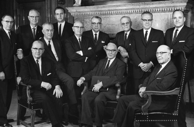 A black-and-white portrait of the Quorum of the Twelve Apostles in 1963. From left to right, seated: Ezra Taft Benson, Mark E. Petersen, Joseph Fielding Smith, LeGrand Richards. From left to right, standing: Gordon B. Hinckley, Delbert L. Stapley, Thomas S. Monson, Spencer W. Kimball, Harold B. Lee, Marion G. Romney, Richard L. Evans, Howard W. Hunter.