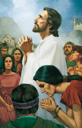 Jesus Christ in white robes, looking upward and standing amid a group of people in the Americas while they all pray together.