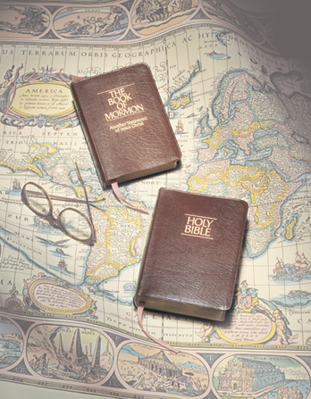 A photograph by Grant Heaton depicting a Book of Mormon and Bible with brown covers lying on an antique map next to a pair of round reading glasses.