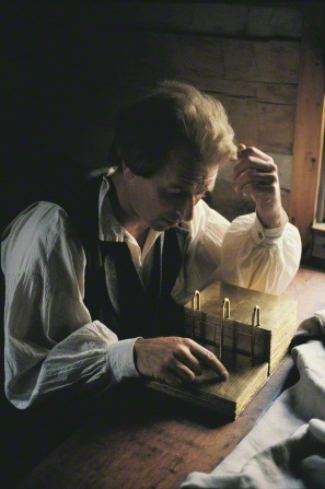 A video still by John Luke depicting Joseph Smith sitting at a desk and translating the gold plates, with light streaming through a nearby window.