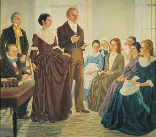 A painting by Nadine Barton of Joseph Smith Jr. and his wife Emma Smith standing before a group of sitting women as they organize the Relief Society.