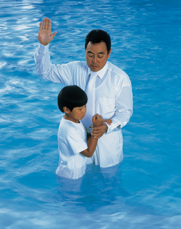 A young boy in a white jumpsuit standing in a large body of blue water to be baptized by a man who is raising his arm to the square.