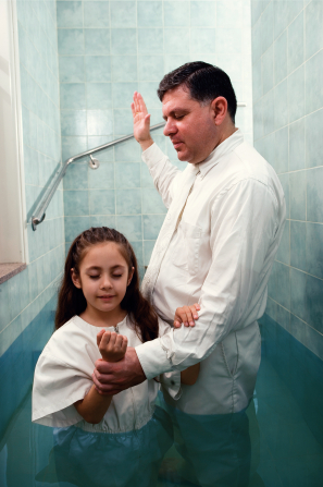 A girl with long brown hair, wearing a white jumpsuit, being baptized in a baptismal font by a man in a white shirt and tie.