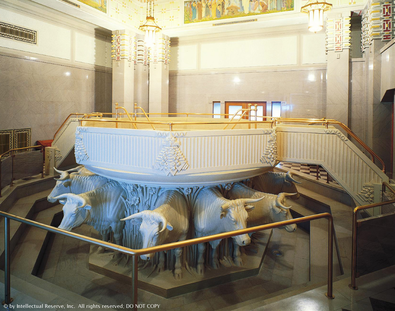 A white baptismal font in the Alberta Canada Temple held on the backs of 12 white oxen.